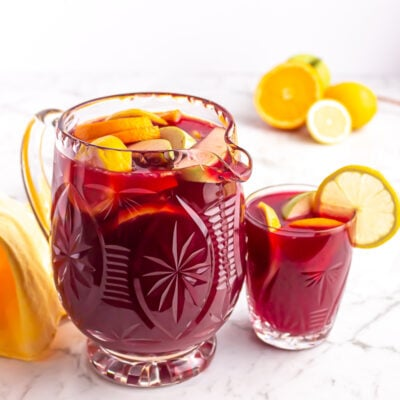 crystal jug of non alcoholic sangria garnished with orange, apple and lemon with a small glass beside it