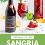 sangria mocktail in a wine glass garnished with an apple fan and lemon round with a jug of Sangria in the background