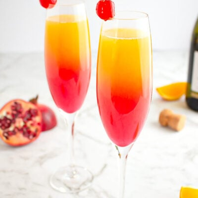 sunrise mocktail in champagne glass garnished with a cherry with pomegranate and orange in the background