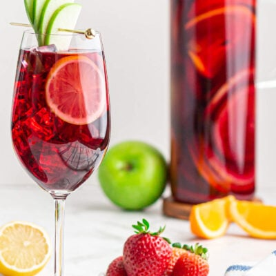 virgin Sangria in a wine glass with an apple fan garnish and a jug of Sangria