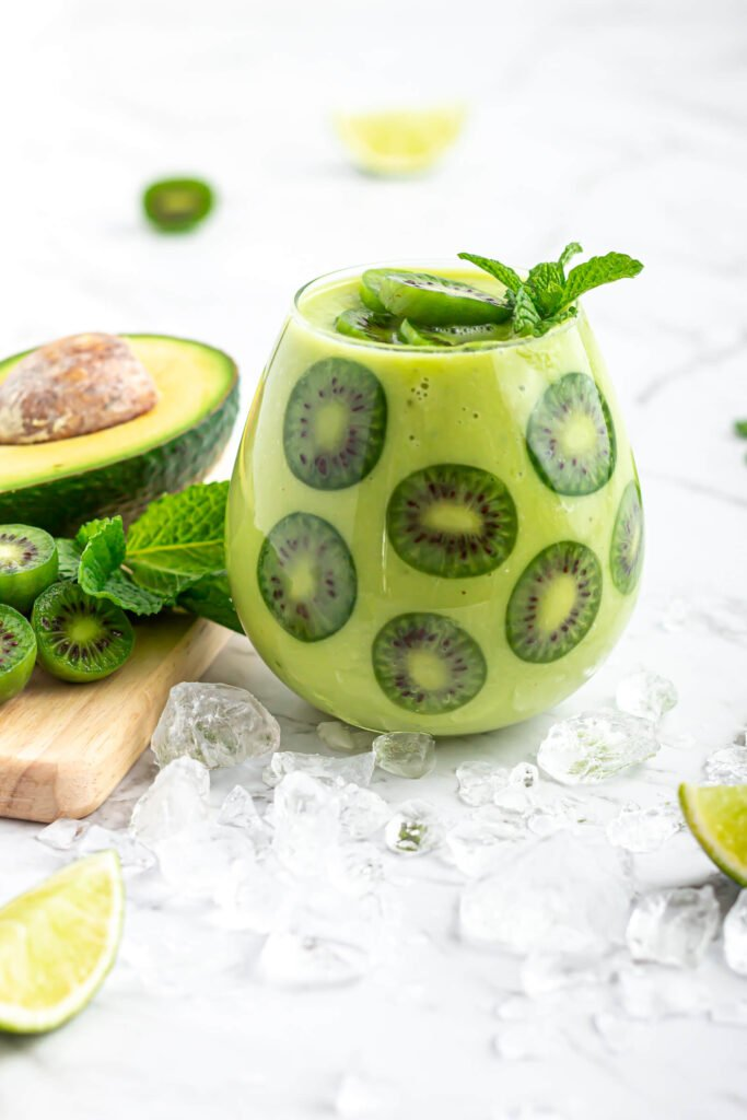 avocado mock ail garnished with kiwi berries in a round glass with avocado, kiwi berries and mint in the background