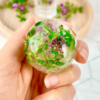 round ice block with frozen flowers in a purple and green colour.