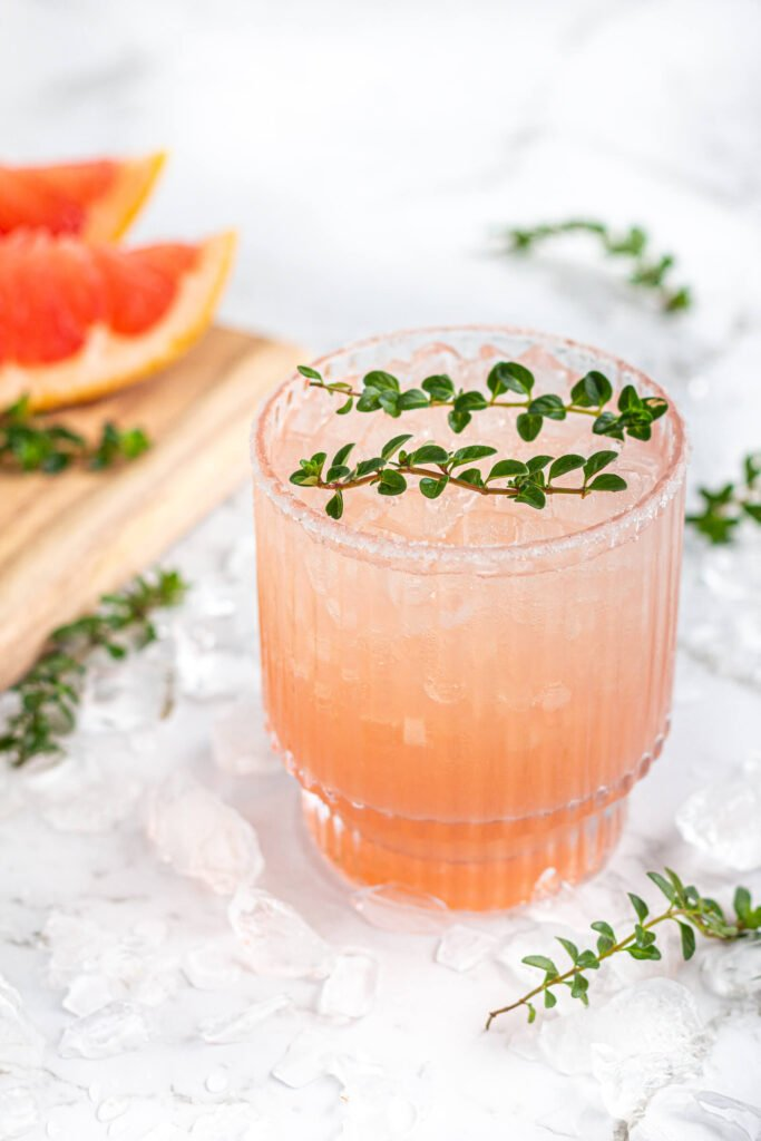pink grapefruit mocktail in a short glass garnished with thyme