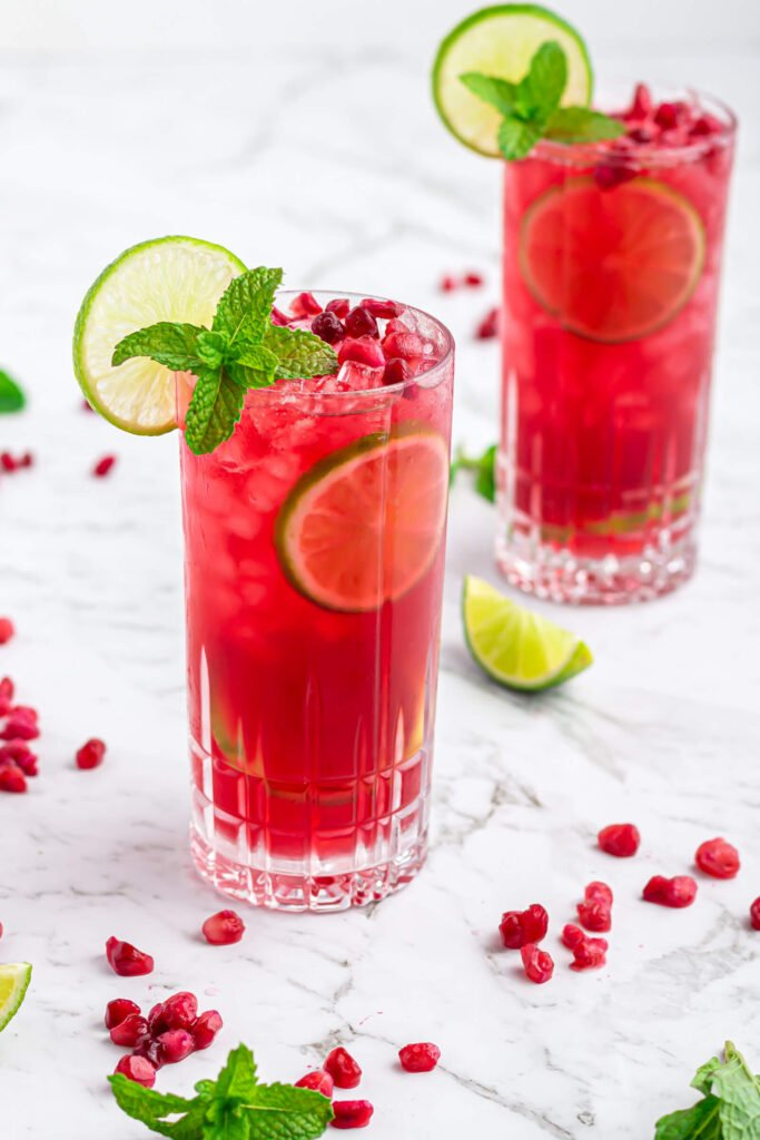 pomegranate mocktail in a tall glass garnished with a lime wheel and mint on a grey and white marble background