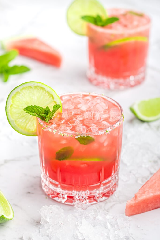 2 watermelon mocktails in short glasses garnished with mint and lime with crushed ice and lime wedges scattered in the background