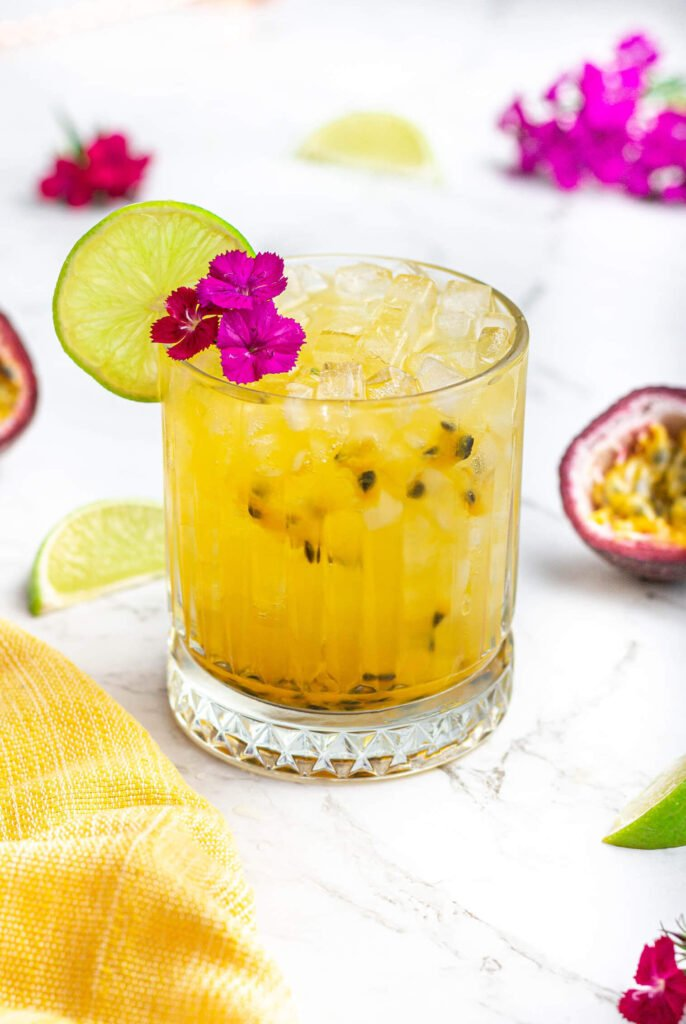 yellow passionfruit mocktail garnished with pink flowers and a lime wheel in a short glass