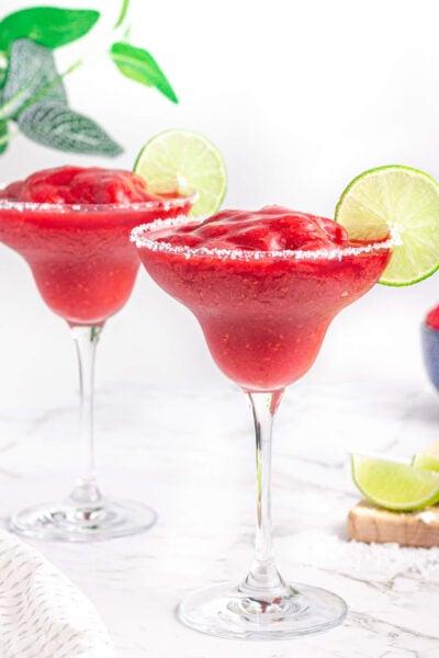 2 virgin raspberry margaritas with salt rims and lime wheel