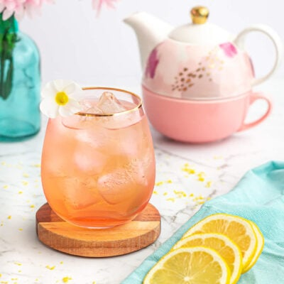 peppermint tea mocktail recipe in a pink glass with a teapot and lemon slices