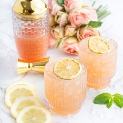 pink guava virgin cocktails garnished with dehydrated lemon with a cocktail shaker and pink flowers