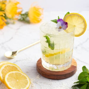 yellow mocktail in a short glass with ice on a wooden coaster garnished with mint and lemon