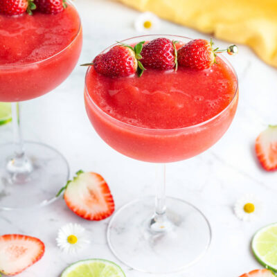 red frozen drink in a coupe glass with 3 strawberries to garnish