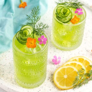 2 green drinks in tall glasses garnished with an orange and pink flower and a sprig of dill