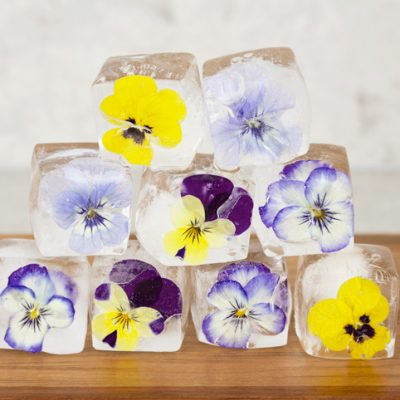 frozen ice cubes with a mix of purple and yellow viola flowers inside, stacked to form a pyramid shape